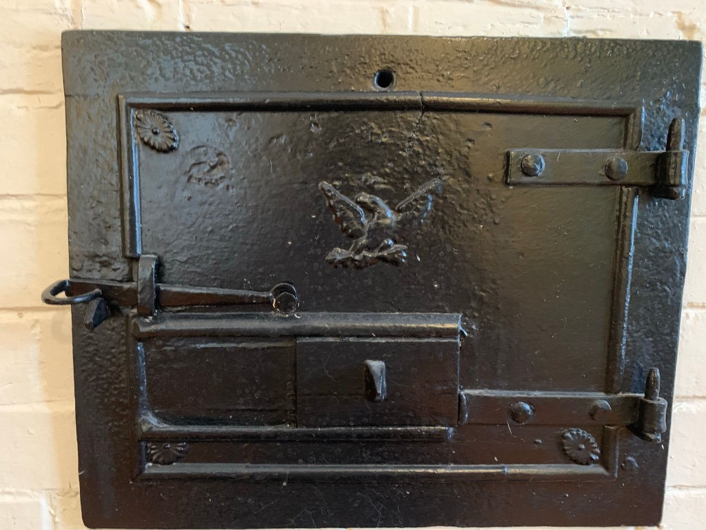 Federal-style cast-iron door at brick oven